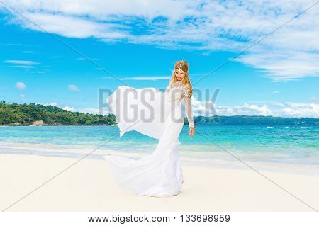 Beautiful blond bride in white wedding dress with big long train having fun on shore sea. Tropical sea in the background. Summer vacation concept.