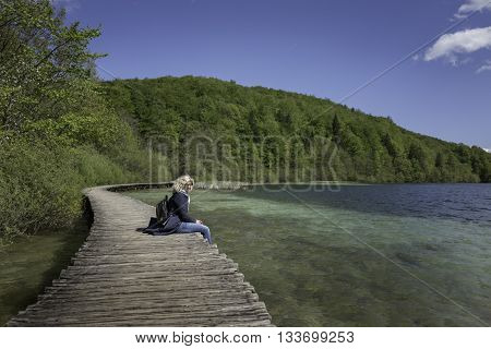 Blonde girl is seating on the bridge near of the lake with stunning blue water