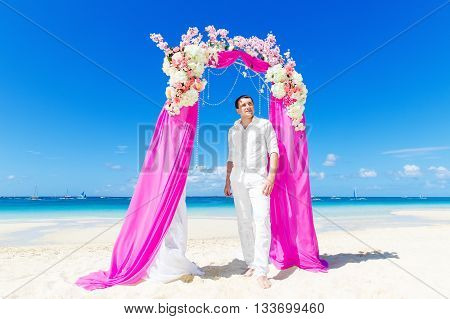 Wedding ceremony on a tropical beach in purple. The groom waits for the bride under the arch decorated with flowers on the tropical sand beach. Wedding and honeymoon concept.