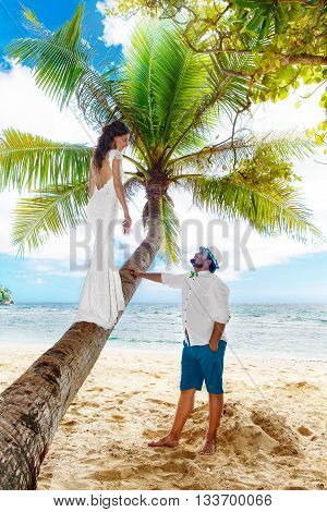 Young beautiful bride in white wedding dress on the palm tree and groom having fun on a tropical beach. Tropical sea in the background. Summer vacation concept.
