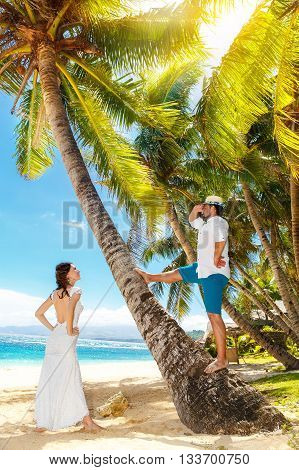 Happy bride and groom having fun on a tropical beach under palm threes. Wedding and honeymoon on the tropical island.