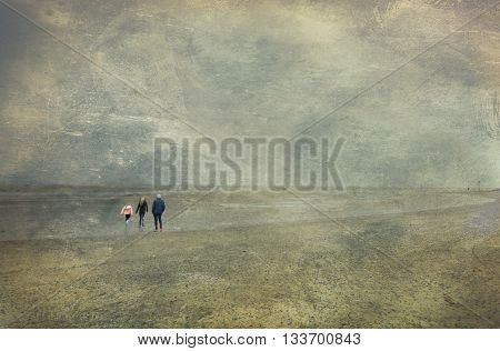 Three people strolling on the beach. Isle of Wight