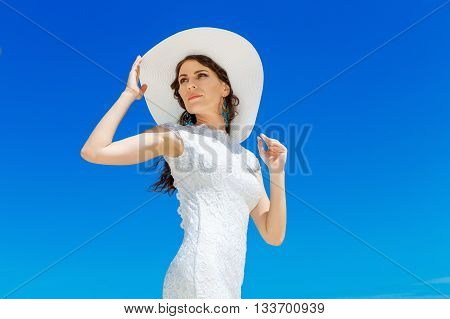 Beautiful brunette bride in white wedding dress and straw hat having fun on shore sea. Tropical sea in the background. Summer vacation concept.