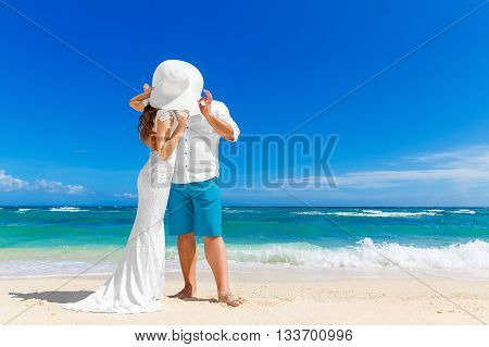 Beautiful brunette bride in white wedding dress and straw hat and groom having fun on shore sea. Tropical sea in the background. Summer vacation concept.