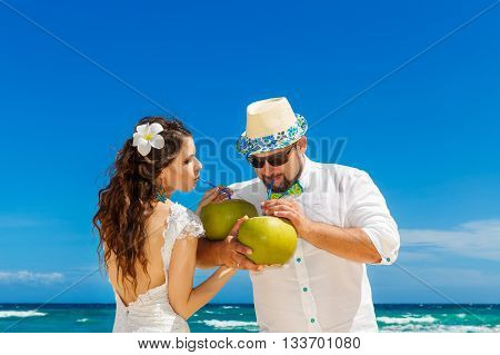Beautiful brunette bride in white wedding dress and groom having fun with coconuts on shore sea . Tropical sea in the background. Summer vacation concept.