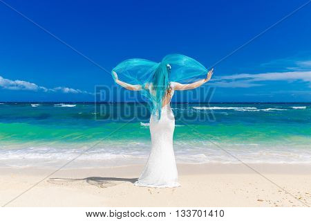 Beautiful brunette bride in white wedding dress with turquoise veil stand on shore sea. Tropical sea in the background. Summer vacation concept.