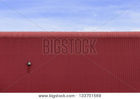 the factory buildingthe factory building made by sheet metal with the blue sky.The sheet metal roof of factory building with the sky.Close-up of the red factory building which made from sheet metal.