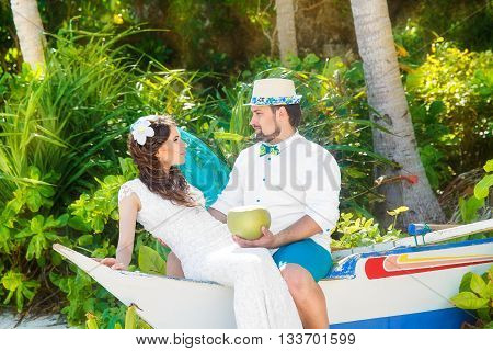 Beautiful brunette bride in white wedding dress with turquoise veil and groom having fun on shore sea under the palm trees. Summer vacation concept.