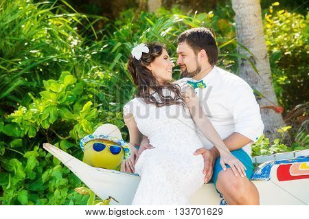 Beautiful brunette bride in white wedding dress and groom having fun on shore sea under the palm trees. Summer vacation concept.