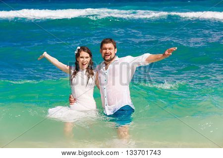 Happy bride and groom having fun in the waves on a tropical beach. Wedding and honeymoon on the tropical island.