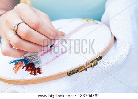 Female hand embroiders angels in the hoop Young girl embroiders a pattern on the white material sweetie brunette engaged in needlework