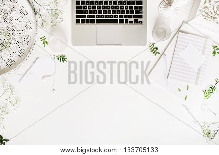 Workspace with laptop headphones pen notebook sketchbook white vintage tray candlesticks on white background. Flat lay top view. Freelancer working place