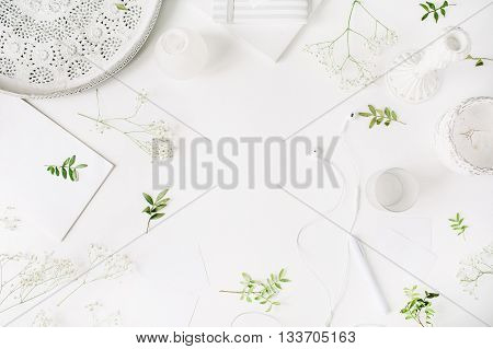 Workspace with headphones pen notebook sketchbook white vintage tray candlesticks on white background. Flat lay top view. Freelancer working place