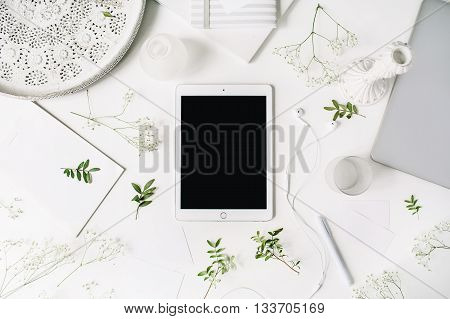 Workspace with tablet laptop headphones pen notebook sketchbook white vintage tray candlesticks on white background. Flat lay top view. Freelancer working place