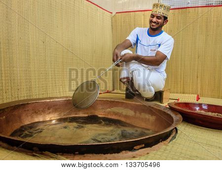 NIZWA, OMAN, MAY 27, 2016: factory worker skims foam from sugar syrup as part of process of making traditional Omani halwa