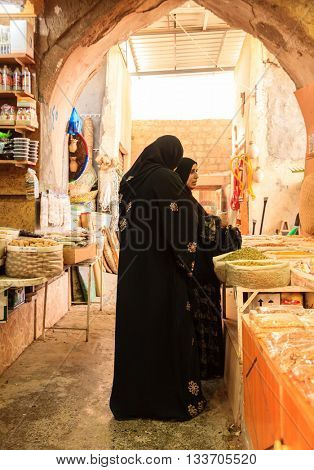 NIZWA, OMAN, MAY 27, 2016: Omani women are shopping at the Friday market in Nizwa, Oman