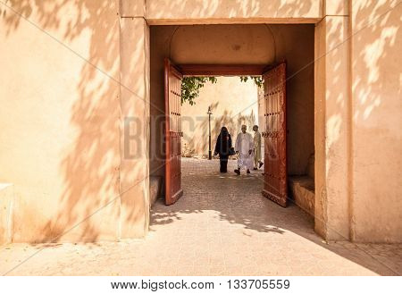 NIZWA, OMAN, MAY 27, 2016: An Omani couple is walking through an alley in the old part of Nizwa village in Oman