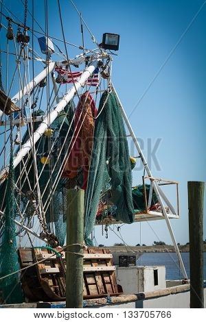 Close up of folded fish and shrimp netting hanging from a boat