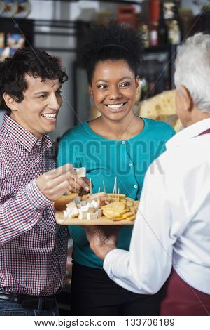 Salesman Offering Cheese Samples To Happy Customers In Shop