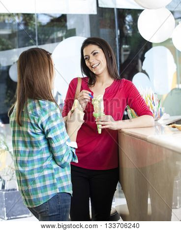 Woman Looking At Daughter While Holding Vanilla Ice Cream Cone