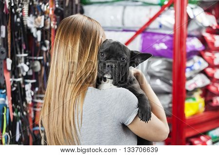Woman Carrying French Bulldog At Pet Store