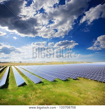 Solar panels with green field and cloudy sky
