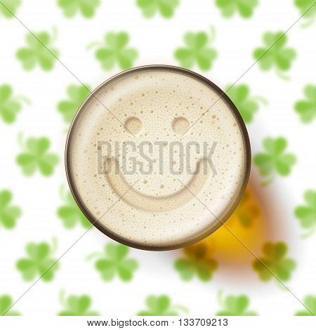 Glass of beer with a smiling face on frothy top, on background with clover leaves. St. Patrick's Day and good mood concept