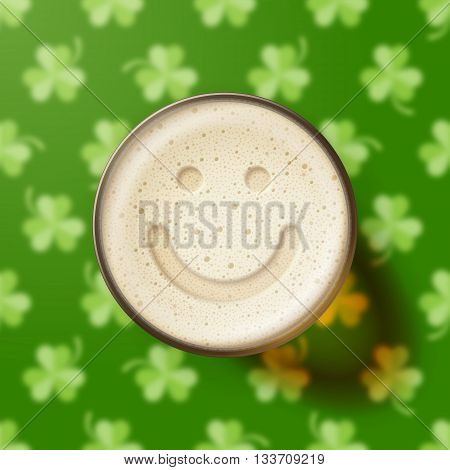 Glass of beer with smiling face on frothy top, on green background with clover leaves. St. Patrick's Day and good mood concept