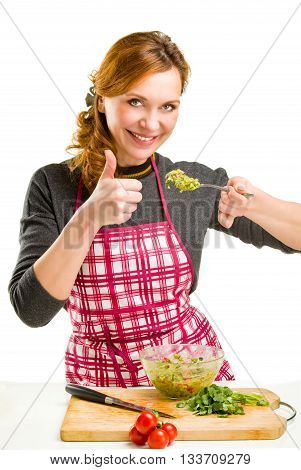 Young Woman Cooking in the kitchen. Healthy Food - Vegetable Salad.