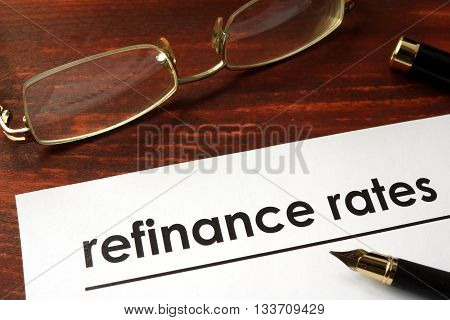 Paper with words refinance rates on a wooden background.