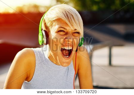 Young woman listening to music via headphones and singing
