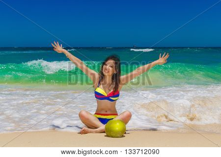 Young beautiful Asian girl with long black hair in bikini drinking coconut water on the beach of a tropical island. Summer vacation concept.