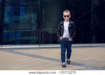 baby boy 7 - 8 years in a leather black jacket and sunglasses walks down the street , on the background of the glass building in the summer, in warm weather
