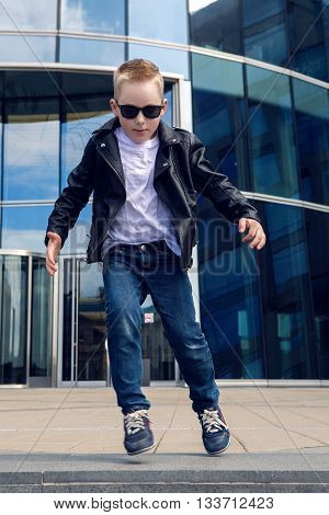 baby boy 7 - 8 years in a black leather jacket dancing in the street on the background of the glass building in the summer, in warm weather