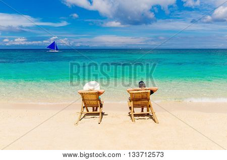 Beach summer couple on island vacation holiday relax in the sun on their deck chairs on the tropical beach. Idyllic travel background.