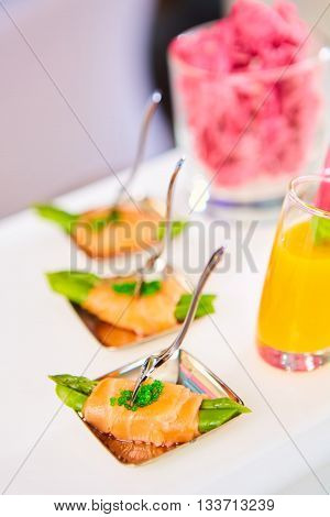 Appetizer plate of sauteed asparagus wrapped in thin slices of smoked salmon and different vegetable juice . Closeup with selective focus and shallow depth of field.