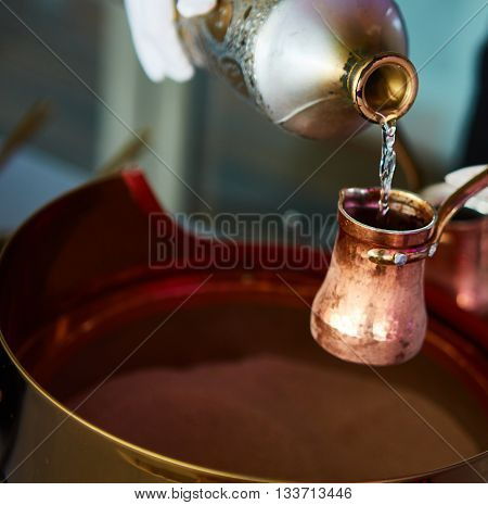 Preparation of Turkish coffee in the cezve in the sand at the cafe bar