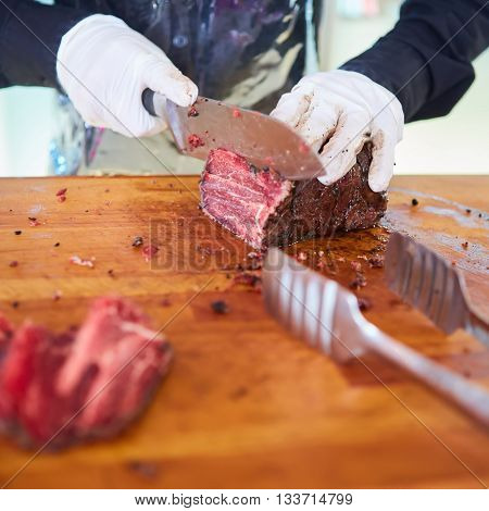 Butcher cutting slices of fresh beef. Shallow dof