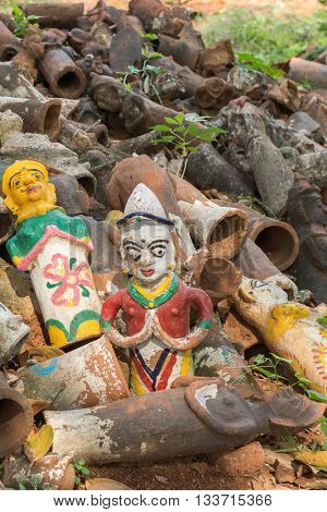 Chettinad India - October 17 2013: Kothamangalam Ayyanar horse shrine. Discarded brown clay figurines have two brightly painted examples intact. Figures used in pregnancy rituals.