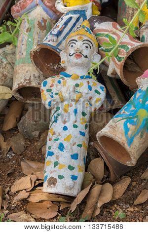Chettinad India - October 17 2013: Kothamangalam Ayyanar horse shrine. Discarded brown clay figurines have one brightly painted example intact. The male looks like a clown in his night gown. Figures used in pregnancy rituals.