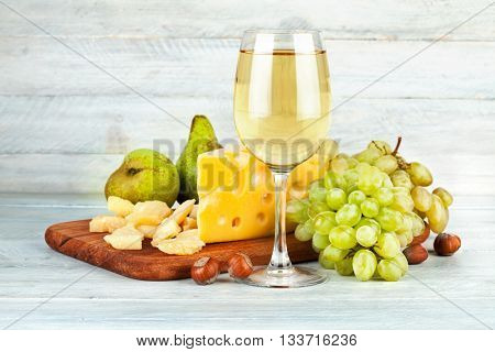 Wineglass white wine with fruits nut and cheese Parmesan still life on vintage wooden board
