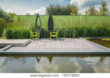 Appeltern, The Netherlands - July 22, 2015: The Gardens of Appeltern is the inspiration garden park in the Netherlands. In this picture 2 green chairs with with a modern outdoor fireplace and storage firewood.