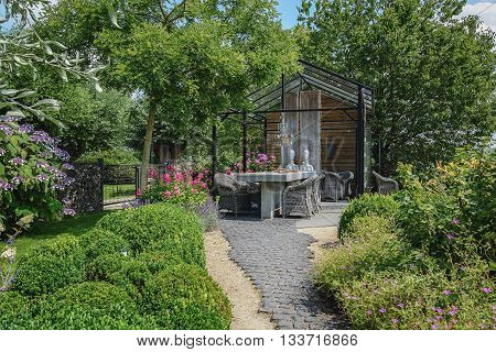 Appeltern, The Netherlands - July 22, 2015: The Gardens of Appeltern is the inspiration garden park in the Netherlands. In this picture a greenhouse with in front two mannequins sitting at a stone table.