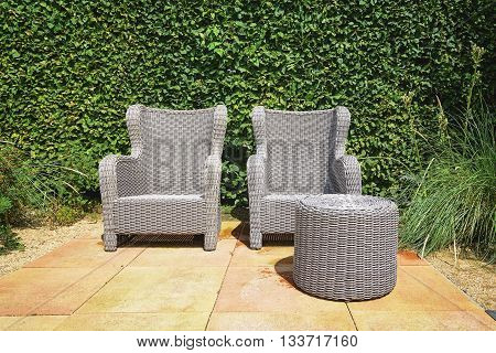 The recreation area with two outdoor chairs and a pouf.
