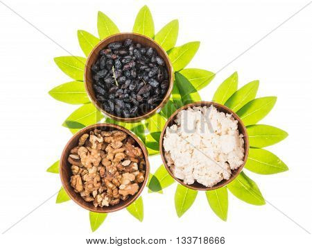 Fresh delicious cottage cheese honeysuckle berries walnuts in brown clay bowl on a background of bright green leaves in the shape of a flower on a white background isolated
