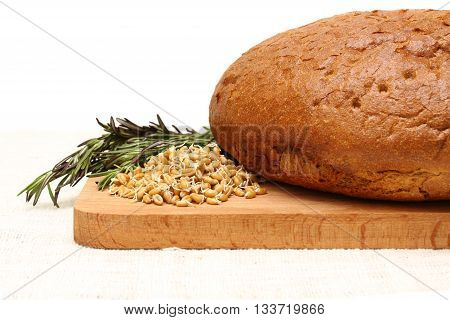 cut bread germinated wheat herb and wooden board on a white linen tablecloths