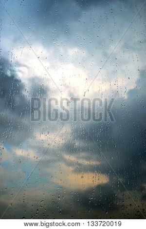 A strong summer storm. Rain drops running down the glass. Beautiful storm clouds hide the sun in the sky.