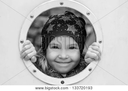 Happy little girl playing hide and seek outdoors ( black and white )