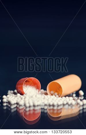 Scattered capsule. Pharmacy background on a black table. Tablets on a black background. Pills. Medicine and healthy. Close up of capsules. Differend kind of pills