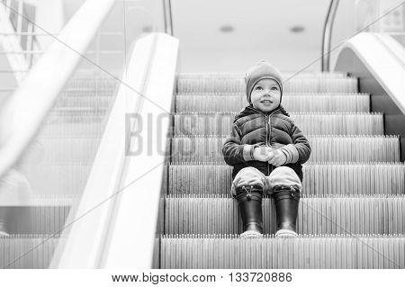 Cute little child sitting on moving staircase in shop ( black and white )